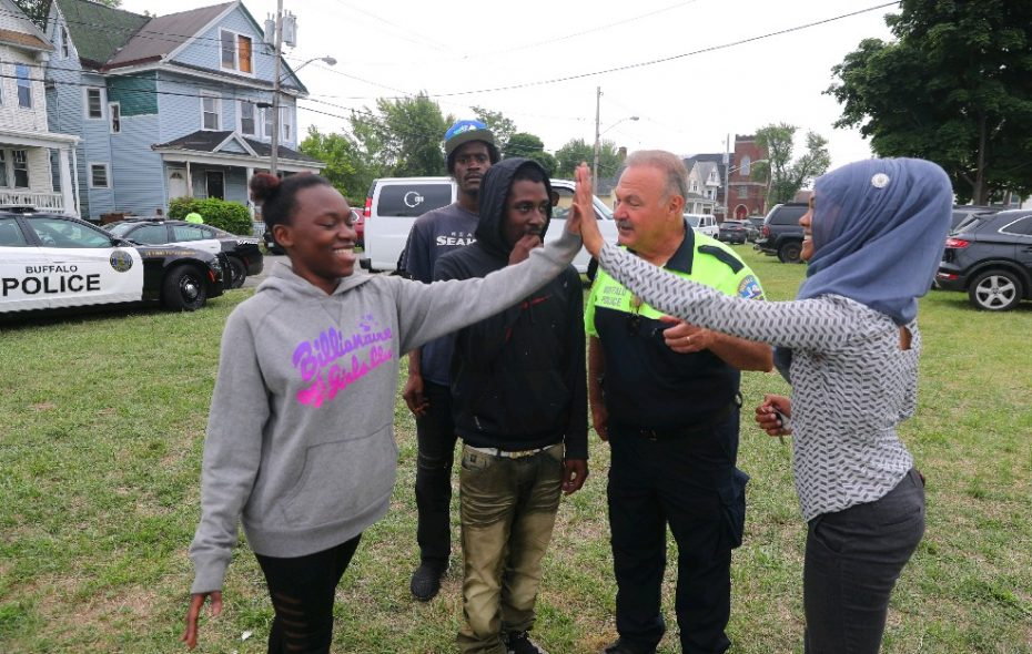 Nahdi Hillman, left, Jayvon Booker and Jay Booker, talk with Buffalo Police Capt. Steve Nichols and Juweria Dahir, external affairs manager for the city's Division of Citizen Services, at a job fair held in August as part of a community policing initiative. (John Hickey/Buffalo News)