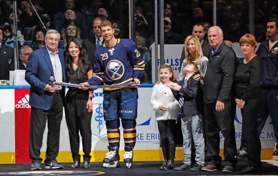 Owners Terry and Kim Pegula present Jason Pominville with a commemorative saber as  his family looks on prior to Saturday's game. (Harry Scull Jr./Buffalo News)