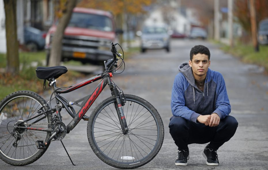 Cristino Almonte, 18, with his bicycle, outside his Black Rock home.  (Robert Kirkham/Buffalo News)