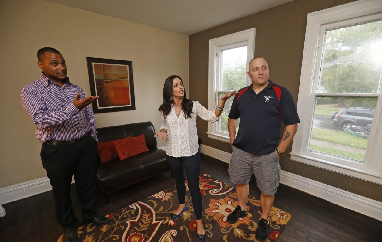In this Sept. 2, 2014, photo, SERV Niagara founder Jennifer D'Andrea, center, with Army veterans Michael Kiff, in shorts,  and James Kenyon, look over one of the group's veterans' apartments in Lockport. (Robert Kirkham/Buffalo News)