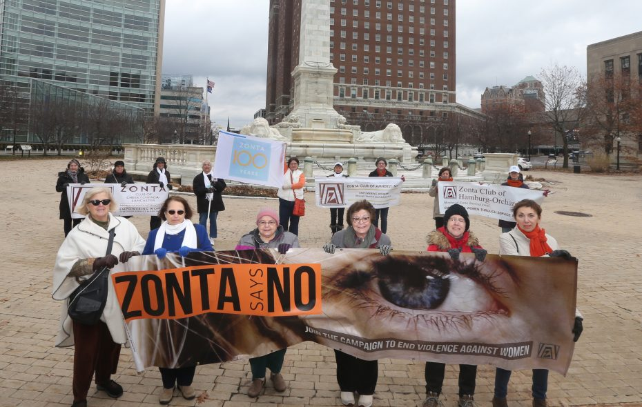 Zonta International members raise a flag to kick off its campaign against gender-based violence Sunday at Niagara Square. (John Hickey/Buffalo News)