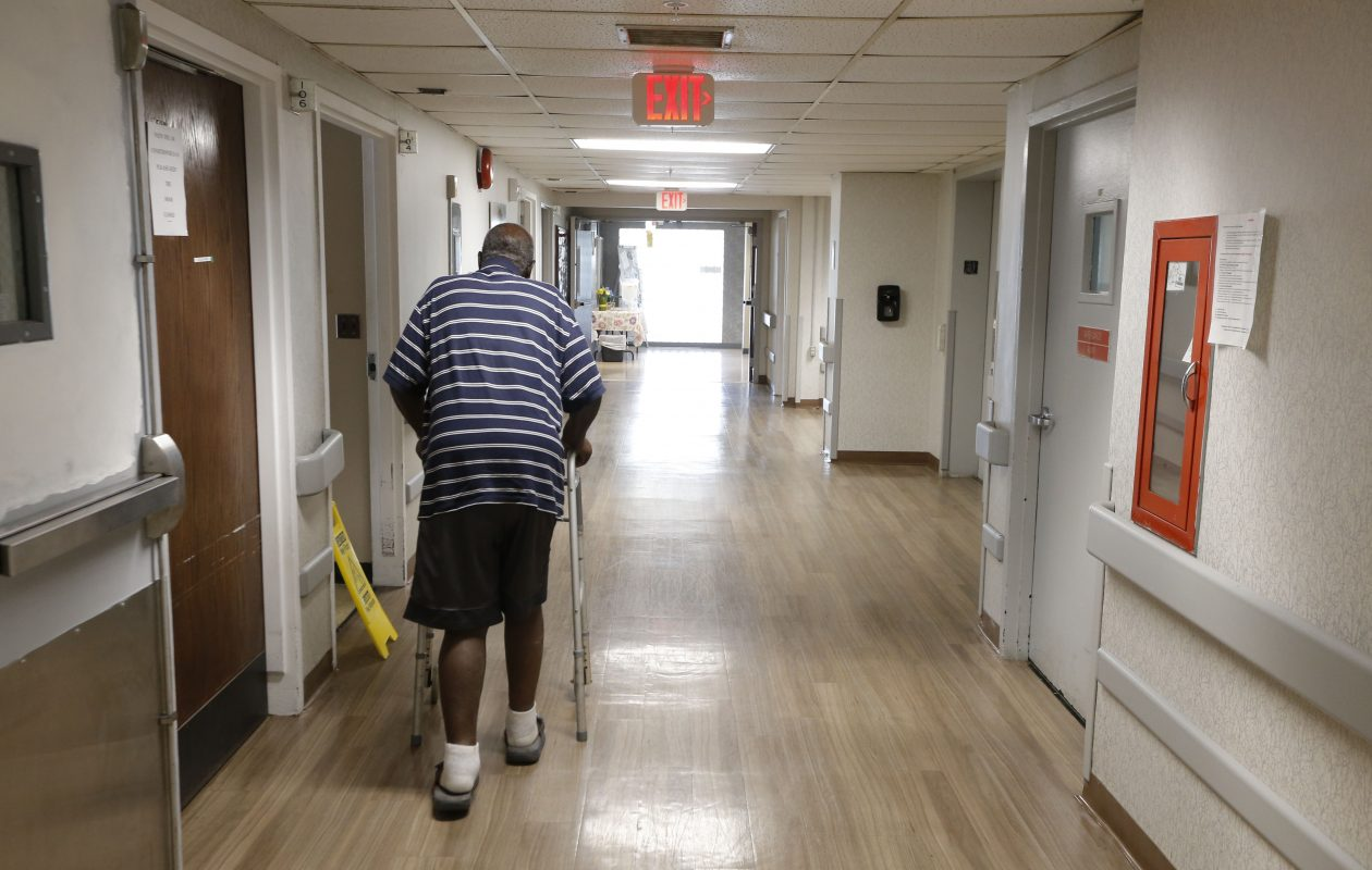 A resident walks down a hallway at Emerald South Nursing and Rehabilitation Center on Delaware Avenue. The troubled facility is due to close at the end of January. (Robert Kirkham/News file photo)