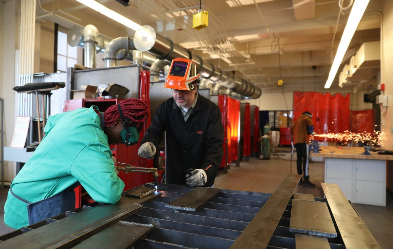 Burgard welding teacher James Ornello helps Janita Prim cut steel in the high school's new welding shop. Now Burgard  wants to use its new facilities to introduce adults to potential jobs in advanced manufacturing. (Sharon Cantillon/Buffalo News)