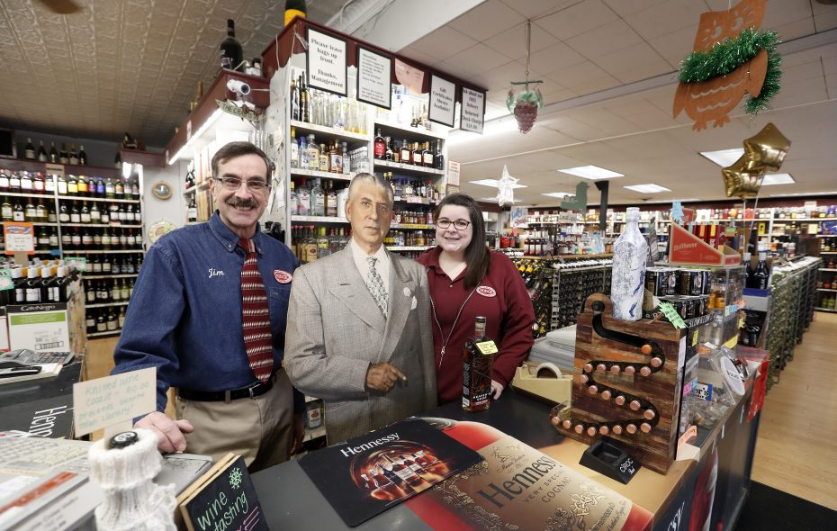 James Pepe and his daughter Kim with a cutout of his grandfather, Anthony Pepe, who founded  the 85-year-old Hodge Liquor on Elmwood Avenue. (Mark Mulville/Buffalo News)