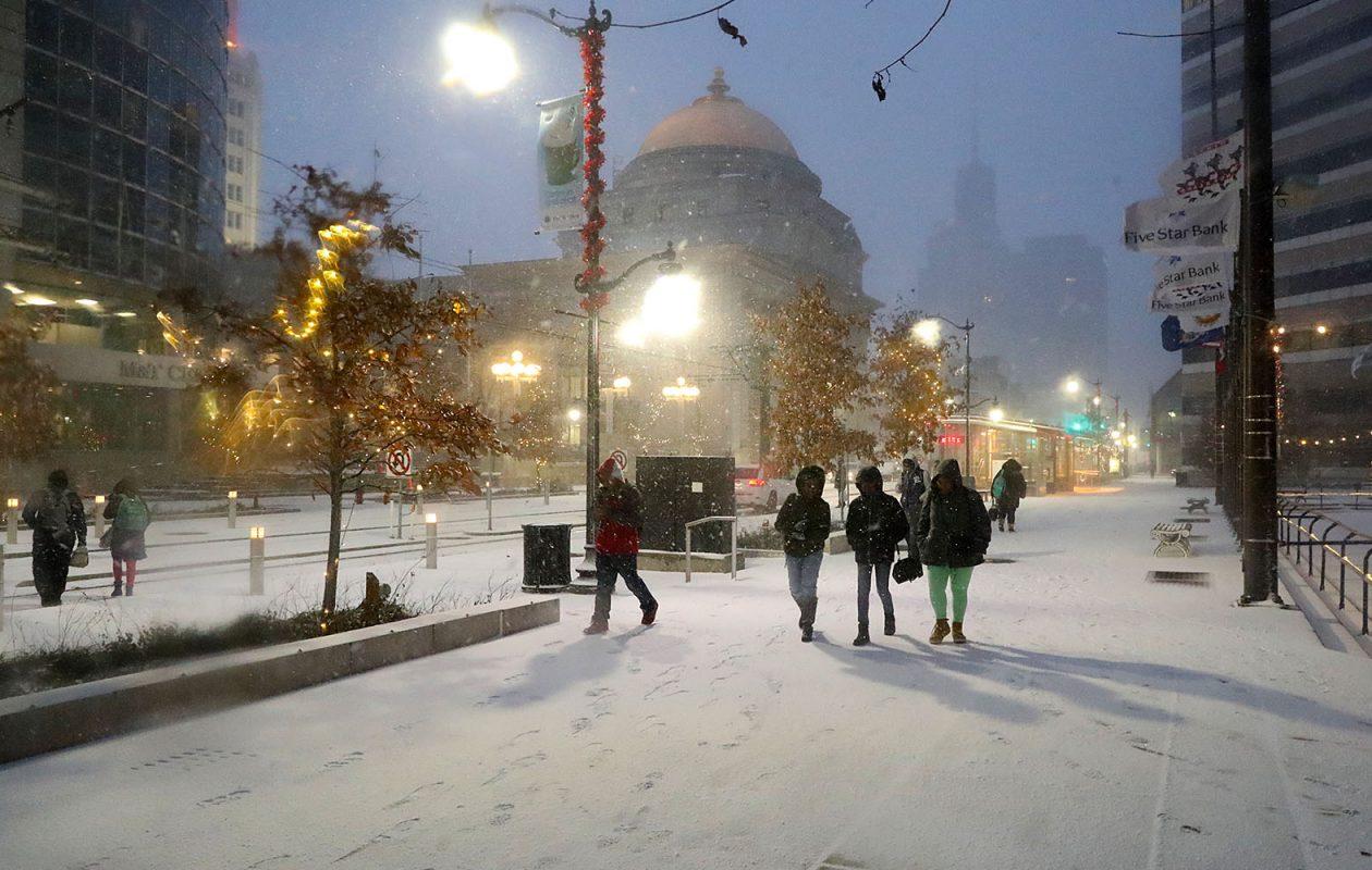Commuters who disembarked Metro Rail walk on Main Street as snow begins to fall in Buffalo on Thursday, Dec. 6, 2018. (John Hickey/Buffalo News)