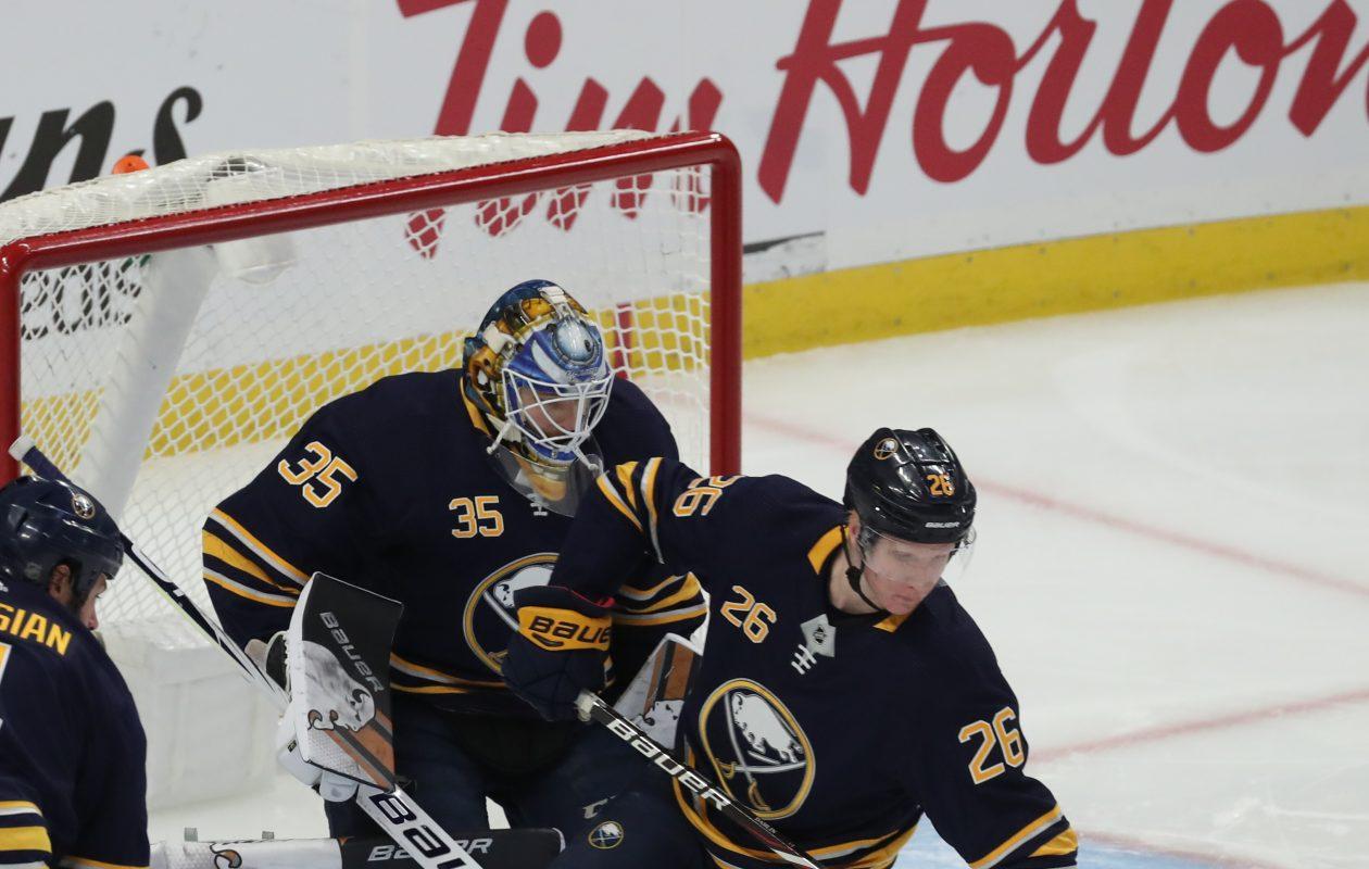 Sabres defenseman Rasmus Dahlin (26) moves to clear the puck in front of goaltender Linus Ullmark. (James P. McCoy/Buffalo News)