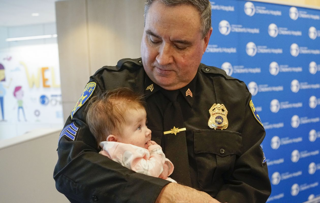 Long-time blood donor Erie County Sheriff Sgt. Sean Higgins holds 4-month-old Evelyn Burkhardt, who was the recipient of Higgins' blood through UNYTS, following an event to showcase the Holiday Heroes campaign at Oishei Children's Hospital. (Derek Gee/Buffalo News)
