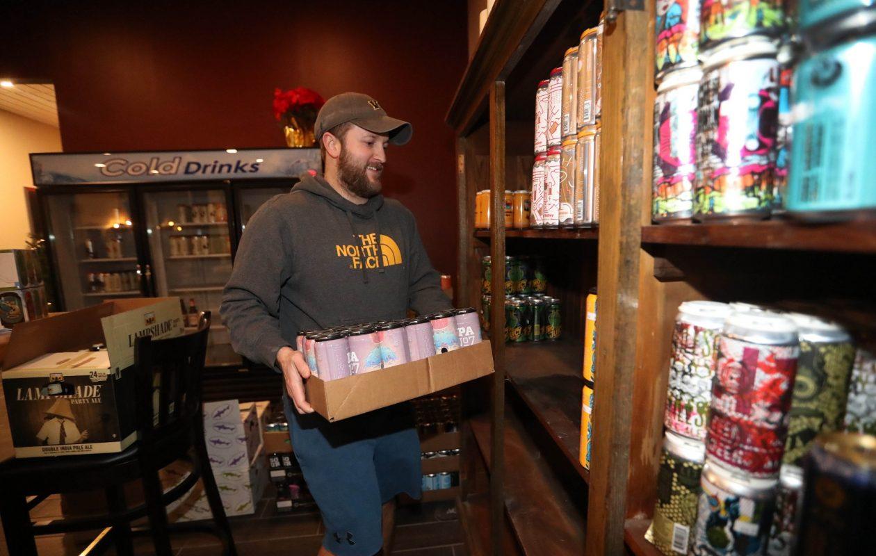 Bottle Rocket Beer Reserve co-owner Nathan Manna stocks the beer shelves. (Sharon Cantillon/Buffalo News)