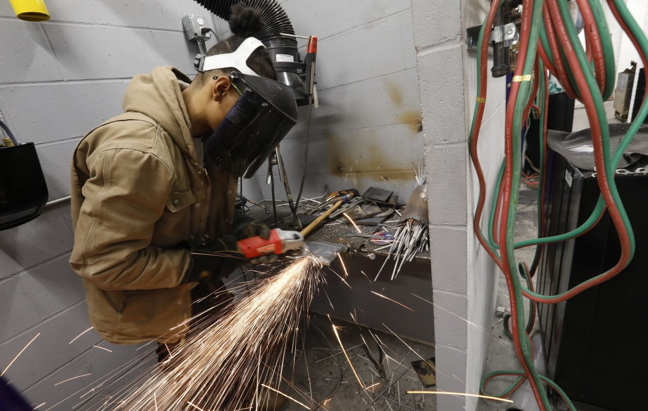 Sparks fly as student Jaelin Grey, 22, uses a grinder to smooth his weld at the Northland Workforce Training Center last month. Many students are unprepared for the center's programs. (Derek Gee/Buffalo News)
