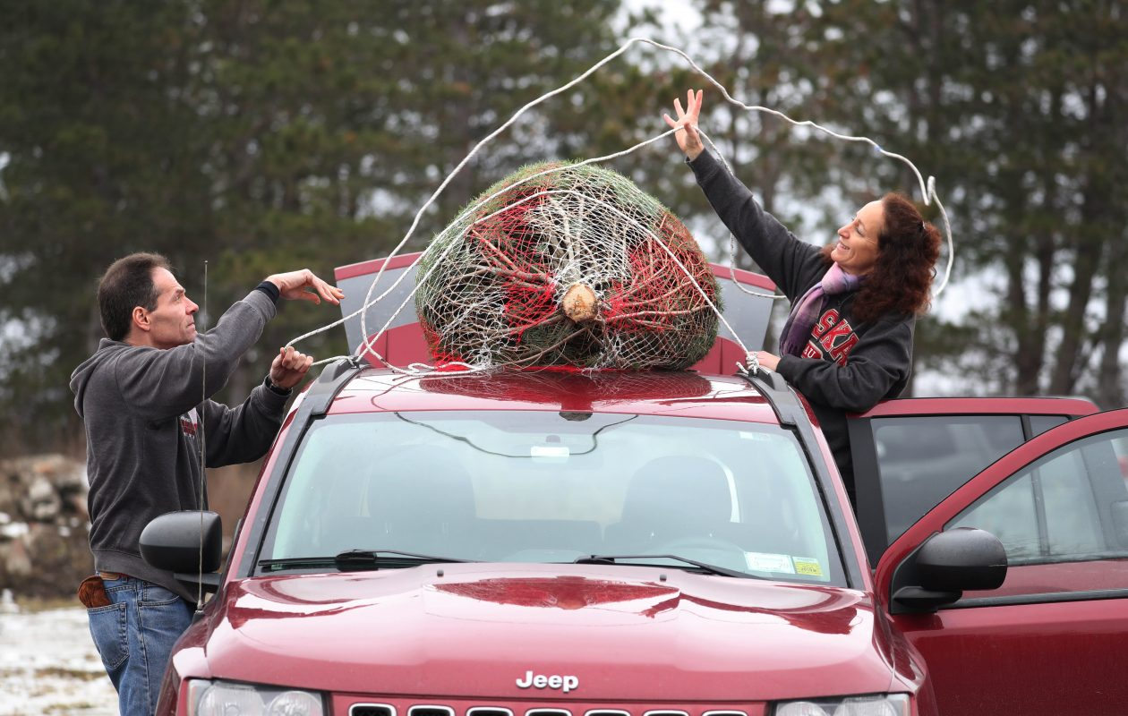 Jurek Plantations, 6600 Strickler Road in Clarence, gives customers the opportunity to cut their own tree or buy pre-cut trees, Saturday, Dec. 15, 2018. Rick and Julie Queeno, of Williamsville, tie the pre-cut tree they just bought to the top of their car. (Sharon Cantillon/Buffalo News)