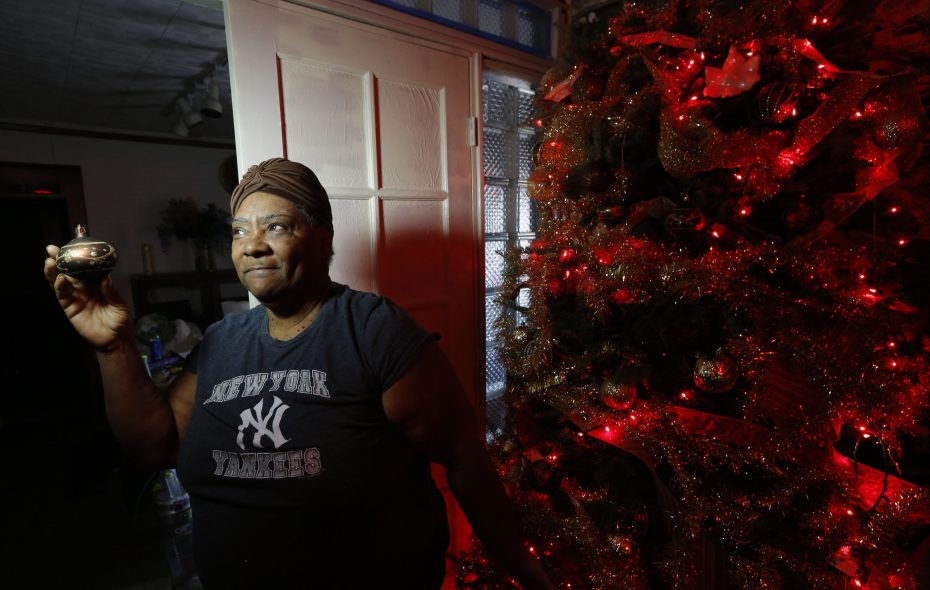 Elizabeth Triggs looks at a Christmas tree ornament Thursday, Dec. 20. Triggs loves to help others through her None Like You/We Care community outreach program. (Robert Kirkham/Buffalo News)