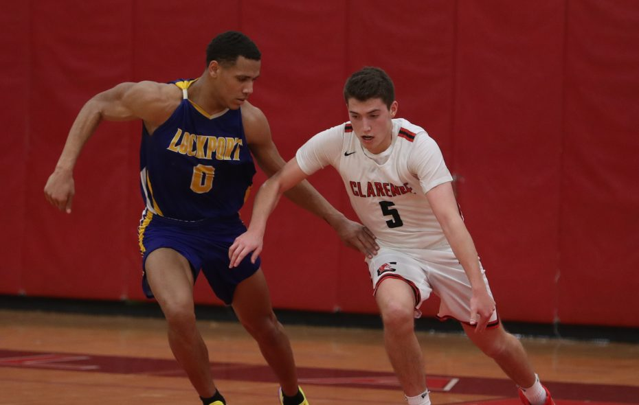 Clarence High School's River Reinhardt dribbles as Lockport's  Malik Brooks guards him in fourth quarter of the Clarence Boys Basketball Tournament championship game at Clarence High School on Friday. Clarence won 66-58. (John Hickey/Buffalo News)