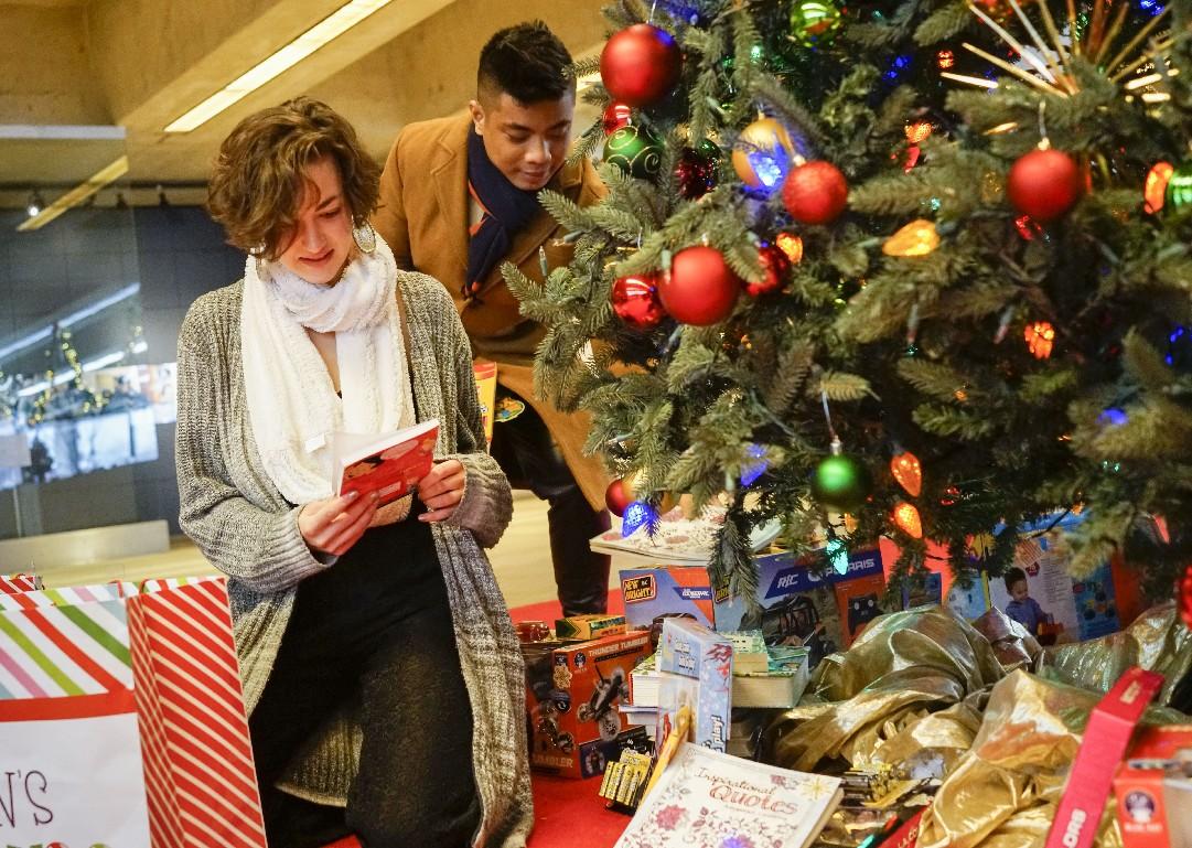 Hamilton cast members Jon Viktor Corpuz and Hannah Cruz deliver toys to the News Neediest Fund in the lobby of The Buffalo News as the holiday season kicked off. (Derek Gee/Buffalo News)