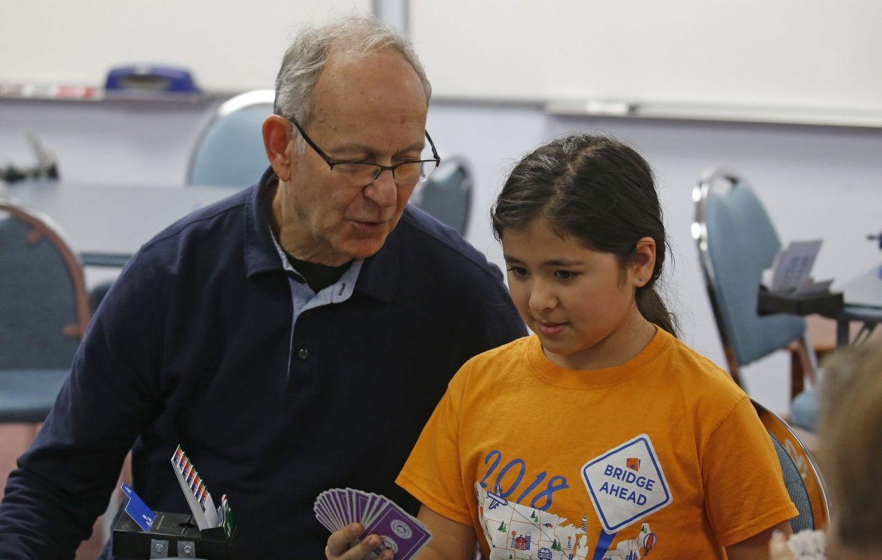 Leondina Passucci, 10, plays in one of her favorite bridge-themed shirts under the instruction of teacher Fred Yellen at the Bridge Center of Buffalo. (Robert Kirkham/Buffalo News)