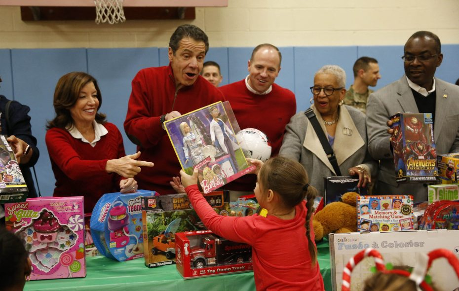 Gov. Andrew M. Cuomo, joined by other elected officials, hands a toy to a student at Dr. Charles R. Drew Science Magnet P.S. 59 Annex on Friday Dec. 21, 2018. (Sharon Cantillon/Buffalo News)