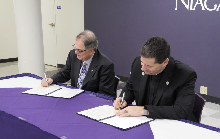 Niagara County Community College interim president William J. Murabito, left, and Rev. James J. Maher, president of Niagara University, sign a cooperation agreement Dec. 6, 2018, in NU's Gallagher Center. (Contributed photo)
