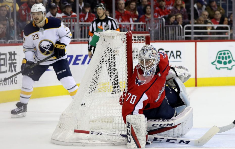 Caps goalie Braden Holtby eyes the puck as  Sabres winger Sam Reinahrt waits for a pass behind the net Friday night (Getty Images).
