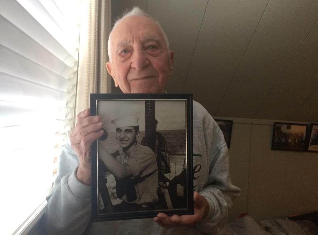 Ed Stone, with an image of himself, as a young sailor. (Sean Kirst/Buffalo News)