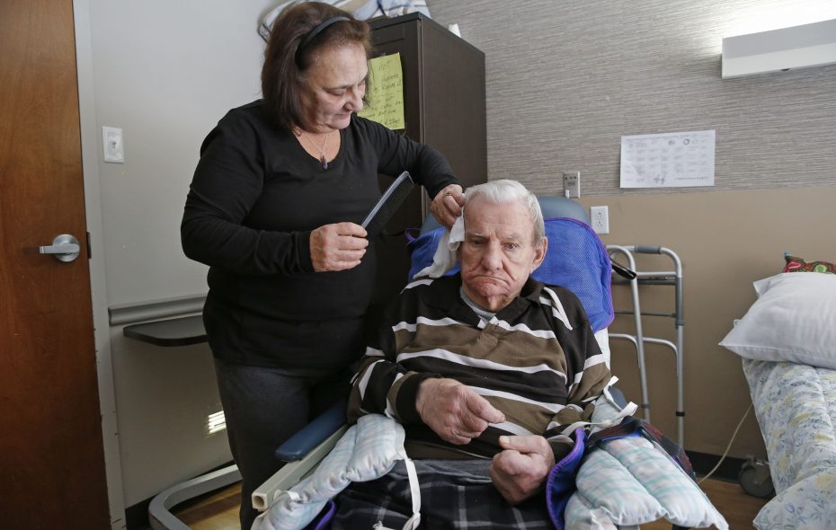 Candy Cutrona combs the hair of her father, Robert Thompson, 87, at the Safire Rehabilitation of Southtowns nursing home in Buffalo on Dec. 7, 2018.  (Robert Kirkham/Buffalo News)