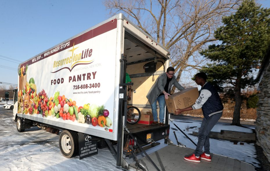 Ian Lapp, left, and Mohammed Hussein, a student from Journey's End Refugee School, help load donated food onto Resurrection Life Food Pantry's 8-foot commercial truck, called Samson, on Thursday, Dec. 13, 2018. Samson was temporarily out of service after the truck was vandalized and its catalytic converters stolen for scrap metal. (John Hickey/Buffalo News)