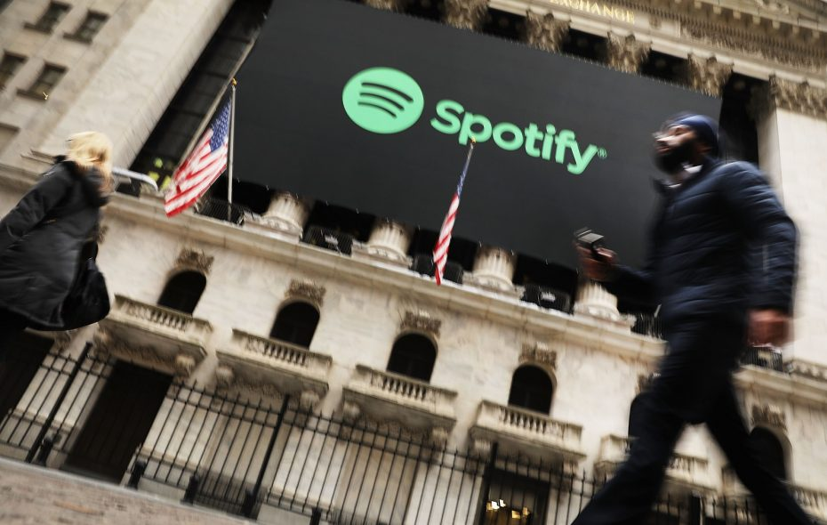 People walk by  the New York Stock Exchange (NYSE) on the morning that the music streaming service Spotify begins trading shares at the NYSE. (Getty Images)