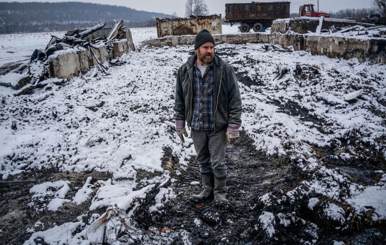 Stew Ritchie with the remains of the barn, after a fire, on the family farm in Little Valley. (Derek Gee/The Buffalo News)