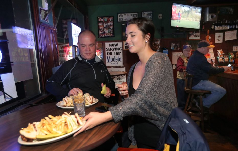Neighbors Pub employee Jillian Canova serves dinner to David Jones, not pictured, and Jordan Goetz, left, of the Town of Tonawanda. (Sharon Cantillon/Buffalo News)