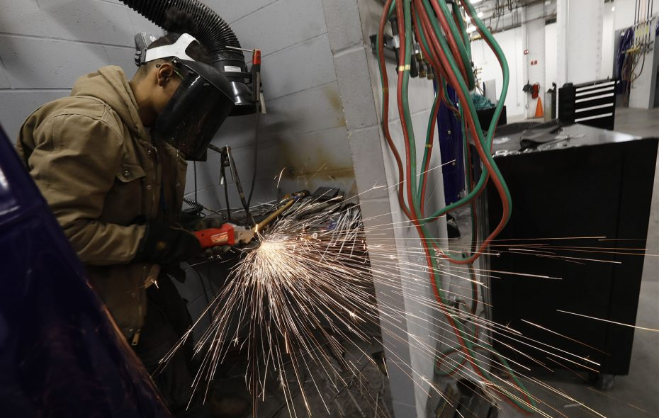 Sparks fly as student Jaelin Grey, 22, uses a grinder to smooth out his weld while practicing for a test in his stall at the Northland Workforce Training Center, Friday, Dec. 14, 2018. (Derek Gee/Buffalo News)