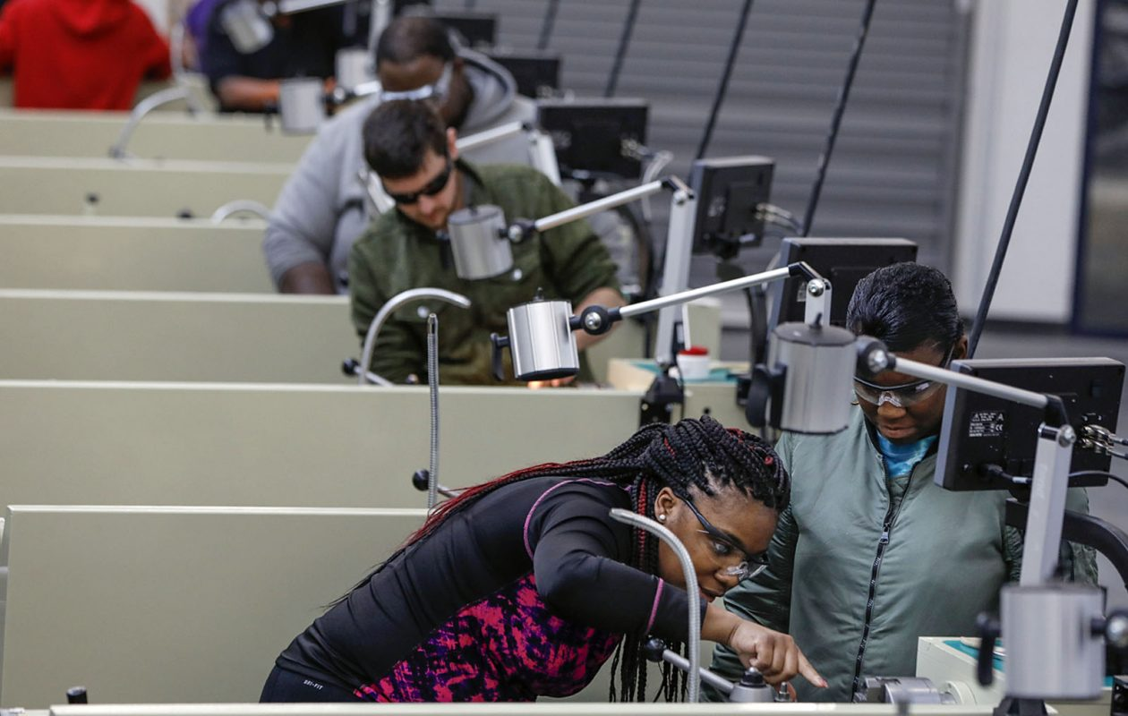Students Aqueelah Chamblis, 27, left, and Rhonda Farr, 37, collaborate while setting up a lathe in the Machine Tool Techonology program at the Northland Workforce Training Center. (Derek Gee/Buffalo News)