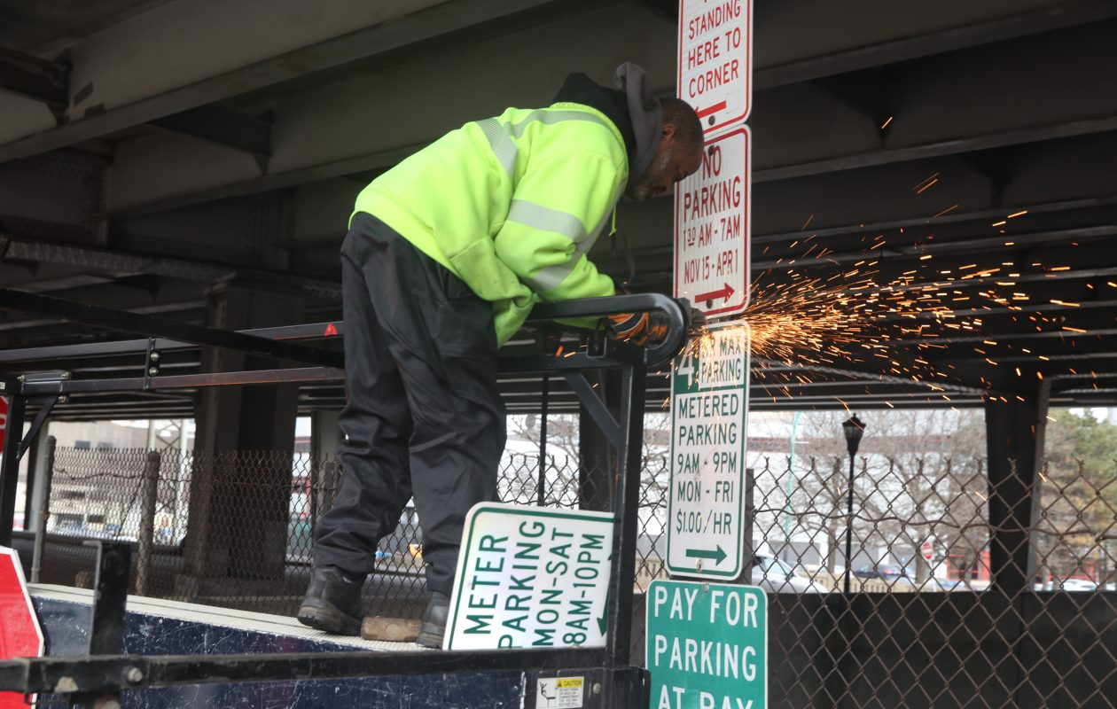 City laborer Ray Williams   takes down an old parking sign and prepares a new one for installation in the Cobblestone District. (John Hickey/Buffalo News)