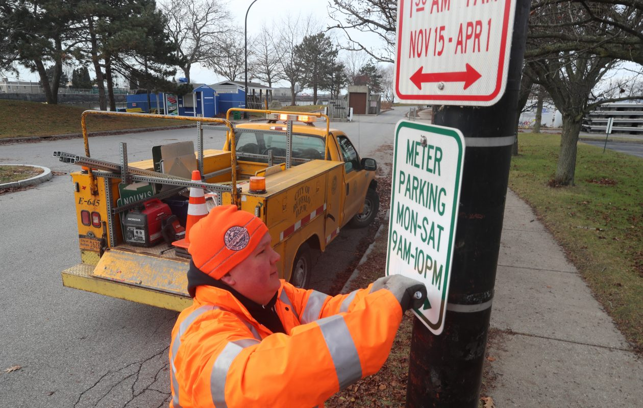 City worker Nick Long  put up a new parking sign in the Cobblestone District last week. The changes were revised after public complaints. (John Hickey/Buffalo News)