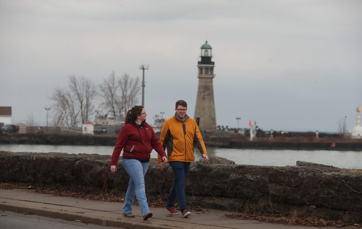 Co-workers Cory Young and Lindsey Boljkovac walk on break from work Tuesday at the Erie Basin Marina. Temperatures remained in the 40s, but a dramatic shift toward winter is expected to start overnight.  (John Hickey/Buffalo News)