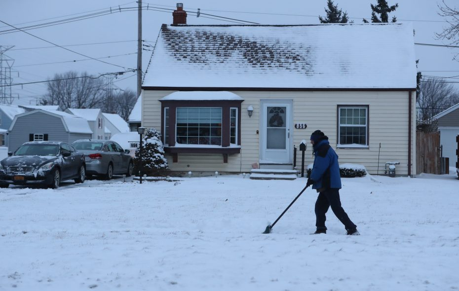 Fritz Stack shovels a modest amount of snow from his driveway and sidewalk  Cleveland Drive in Cheektowaga this morning. (John Hickey/Buffalo News)