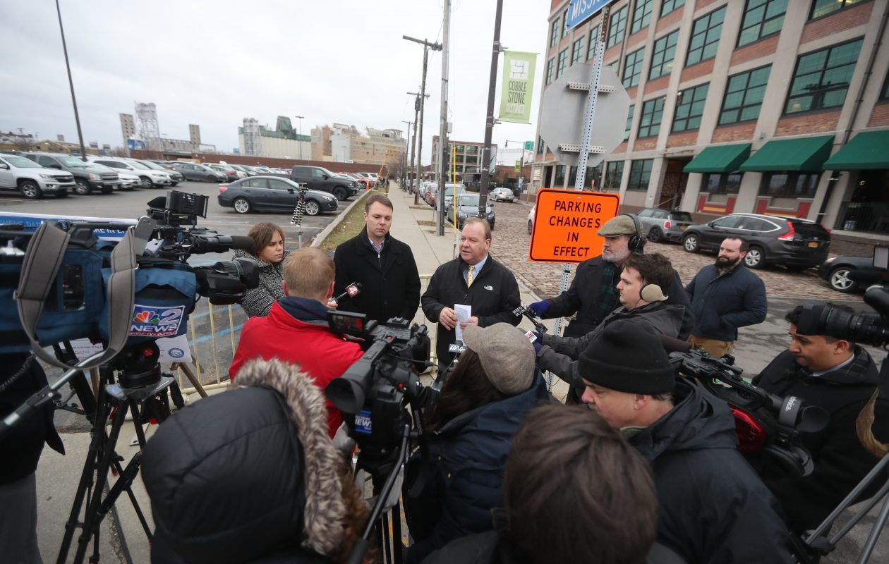 City Engineer Michael Finn, top left, and Parking Commissioner Kevin Helfer, top right, explain the new parking plan in effect in Buffalo. They held a news conference at Perry and Mississippi streets on Thursday, Jan. 3, 2019. (John Hickey/Buffalo News)