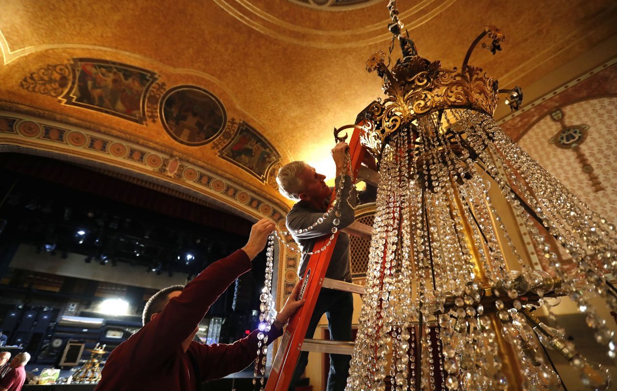 Al LeTeste, right, and Neil Lange, left, replace the cleaned crystals on the chandelier in the Riviera Theatre in North Tonawanda Tuesday.    (Mark Mulville/Buffalo News)