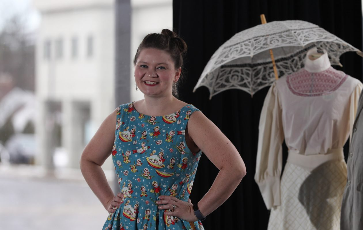 Kari Drozd, resident costume designer at MusicalFare Theatre in Amherst, wears a favorite dress in front of some costumes she is working on for the MusicalFare  production of 'Ragtime,' Feb. 13-March 17.  Her designs have been seen in many local theater productions.  (Sharon Cantillon/Buffalo News)