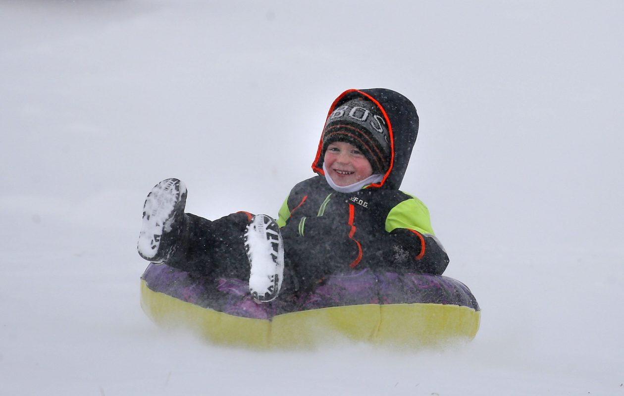 Eddie Kessel riding his tube on the sledding hill at Chestnut Ridge Park in Orchard Park  on Saturday. (Mark Mulville/Buffalo News)
