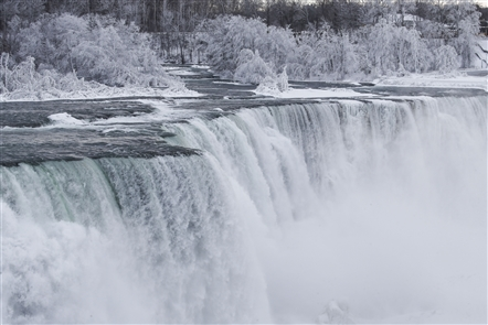 Freezing temperatures have once again transformed the landscape around Niagara Falls into a picturesque winter spectacle of trees sheathed in white and sections of the Niagara River crusted over with ice as the current slides beneath.