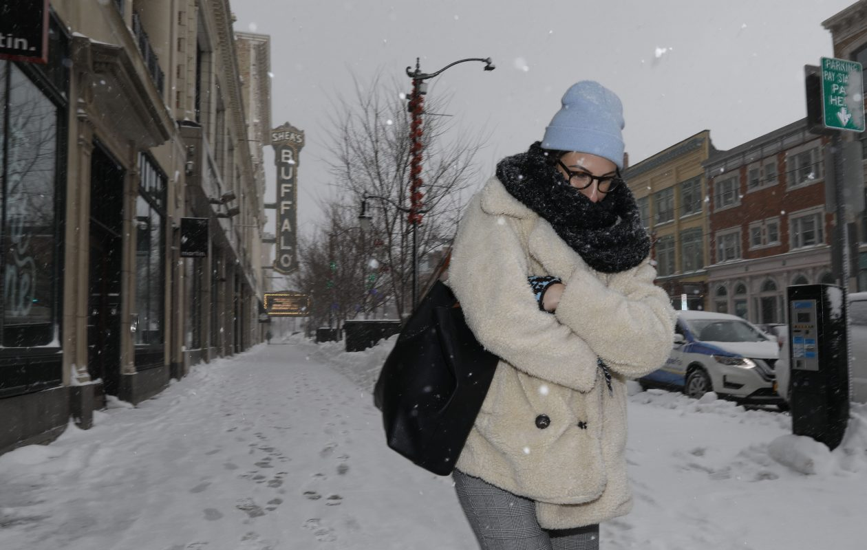 Paige Tilley braces herself against the snow while walking down Main Street. Another round of heavy lake-effect snowfall is expected today along with the arrival of frigid polar air. (Derek Gee/Buffalo News)