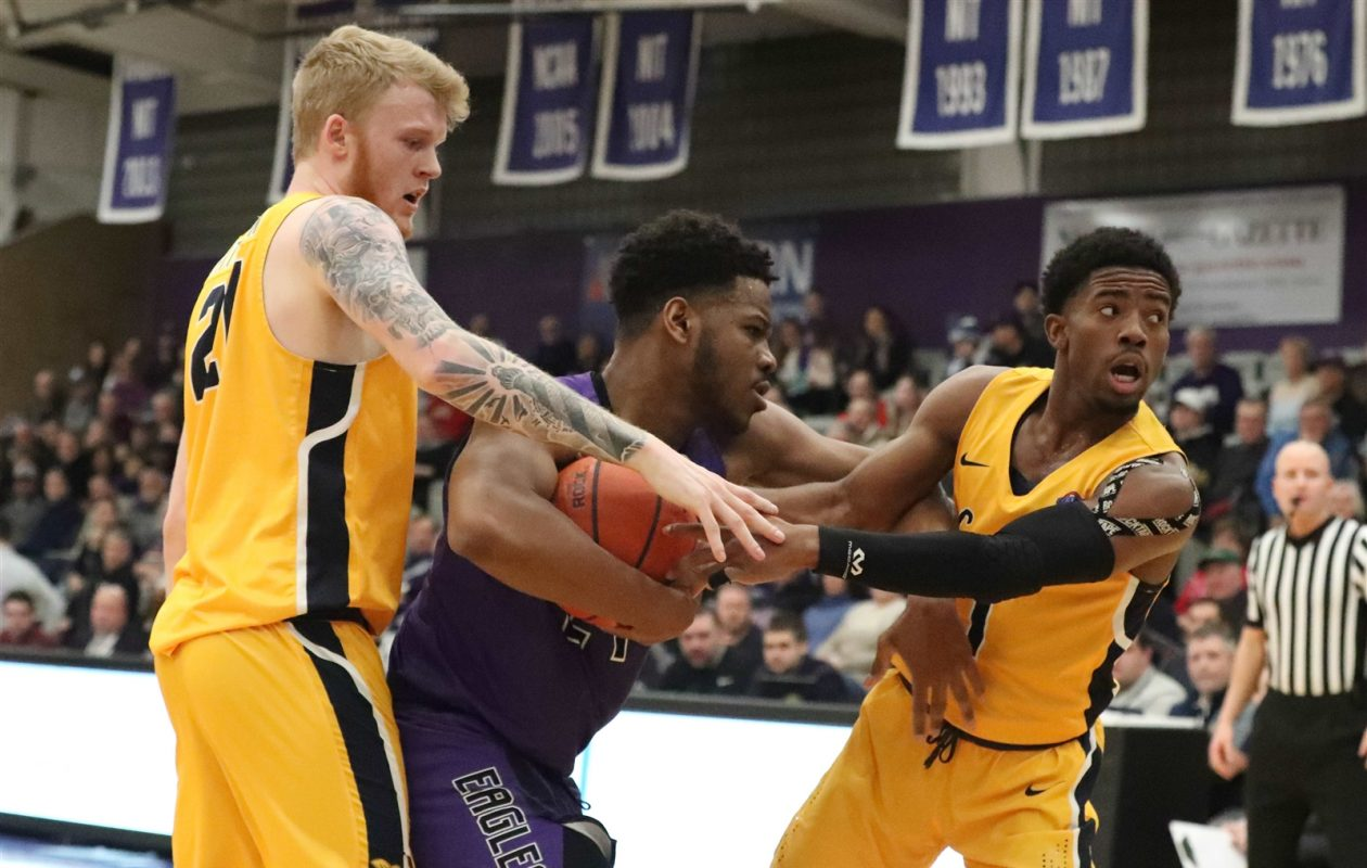Niagara Purple Eagles forward Greg King is called for a foul while covered by Canisius Golden Griffins forward Scott Hitchon and Canisius Golden Griffins guard Malik Johnson in the first half. (James P. McCoy/Buffalo News)