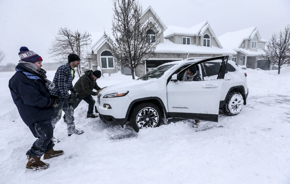 Debbie Koeppel has her car pushed out from a snow bank on the side of the road by Justin Sturman, Tom Cunningham and Maddy Koepple on Grand Island, N.Y., on Wednesday, Jan. 30, 2019. (James P. McCoy/Buffalo News)