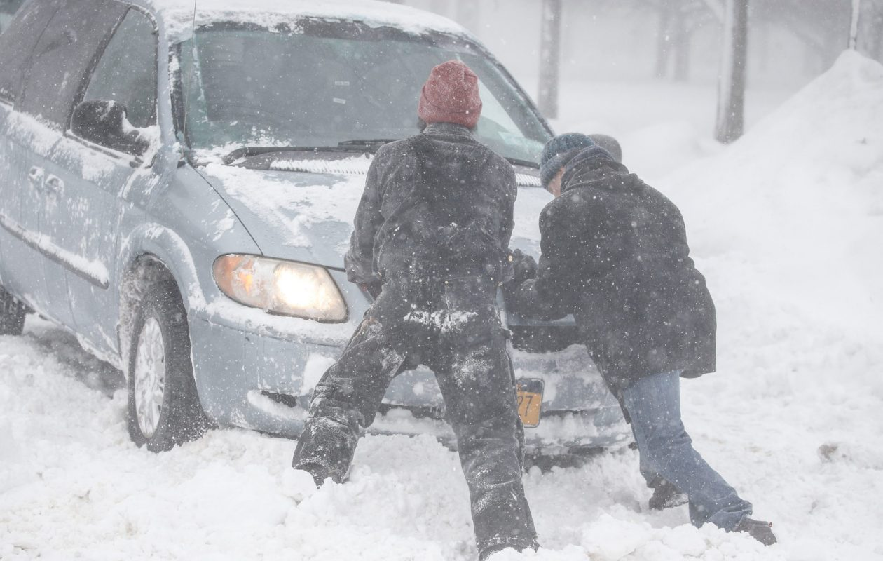 Good Samaritans help push a motorist get out of a snowbank Thursday on South Johnson Park. (Derek Gee/Buffalo News)