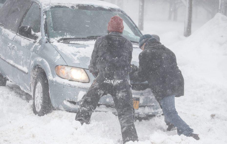 Good Samaritans help push a motorist get out of a snowbank Thursday on South Johnson Park. (Derek Gee/Buffalo News)