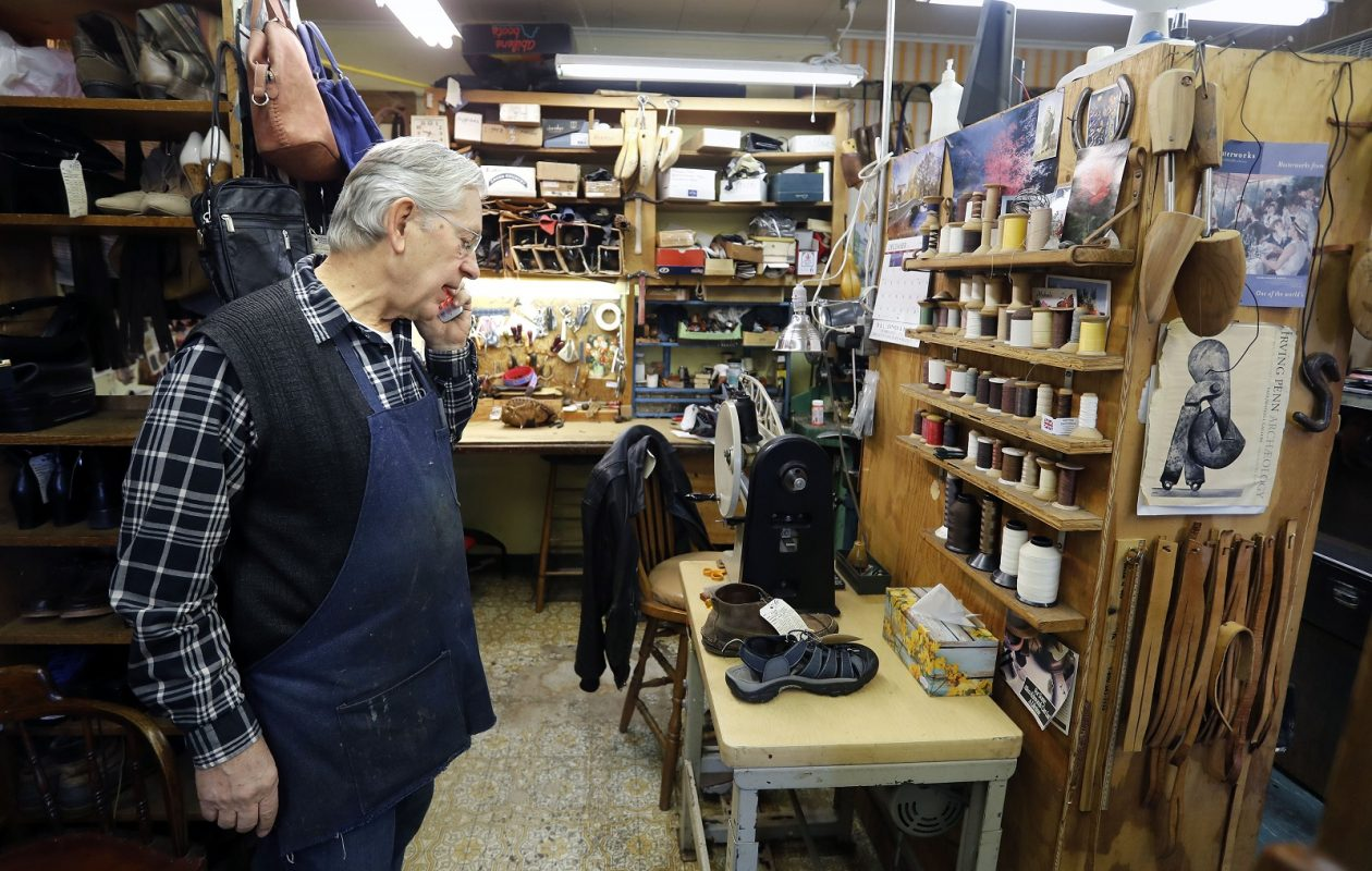 Shoemaker Tom Burakowski answers a customer's phone call at his shop, the Shoemaker's Bench in Hamburg. (Mark Mulville/Buffalo News)