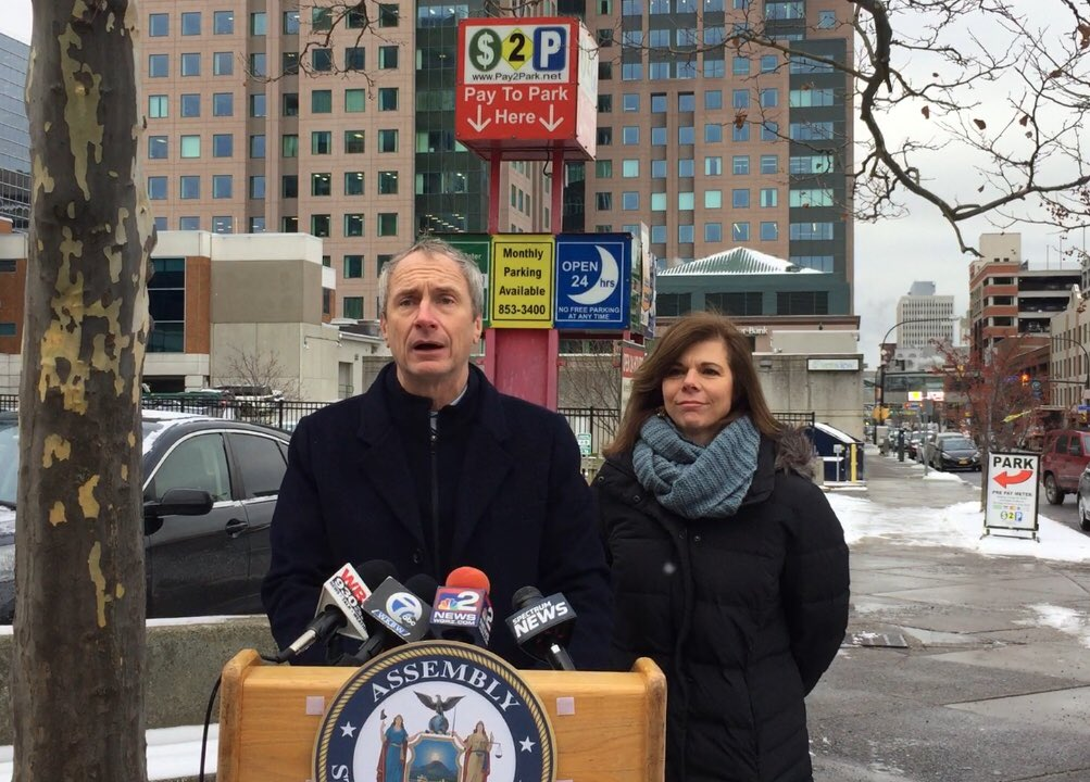 Assemblyman Sean M. Ryan, with Assemblywoman Monica P. Wallace, announces legislation to prevent predatory practices in private parking lots. Part of issue, Ryan said, is confusing signs like one behind him. (Keith McShea/Buffalo News)