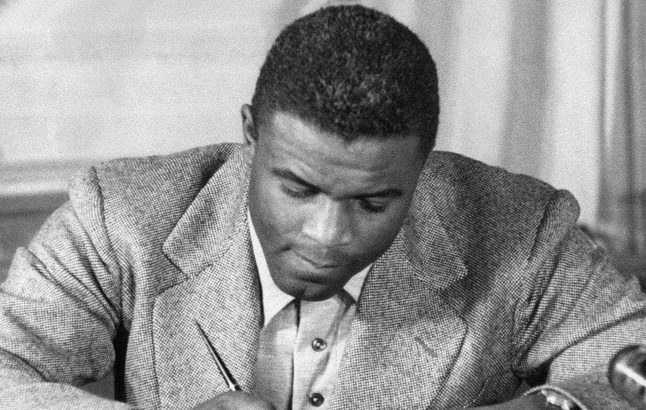 Jackie Robinson as he signs a then-record contract to play for the Brooklyn Dodgers. (STR/AFP/Getty Images)
