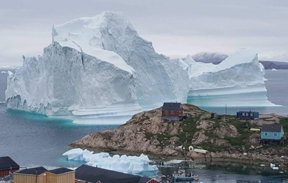 A picture taken on July 13, 2018, shows an iceberg behind houses and buildings after it grounded outside the village of Innarsuit, an island settlement in the Avannaata municipality in northwestern Greenland. (MAGNUS KRISTENSEN/AFP/Getty Images)