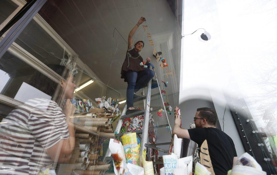 Elmwood Village art teacher Ashley Smith, center, artist Elvi Jo Dougherty, left, and Matt Lehner, right of Buffalo Lab, help install the artwork of 350 students in the window of Hyatt's All Things Creative on Main Street in 2016. (Mark Mulville/News file photo)