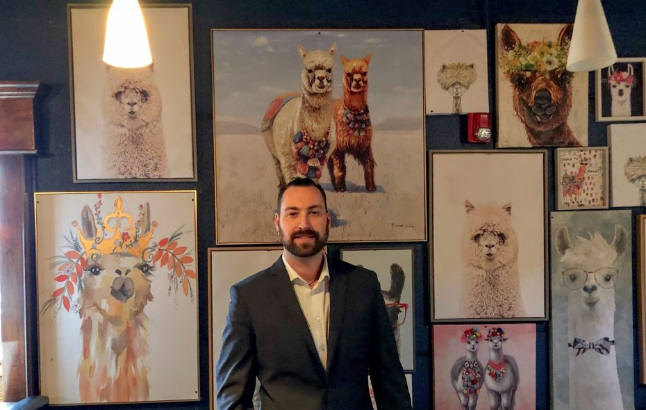 Brandon Carr, owner of The Quarter, stands in front of the llama wall in the Llama Lounge, which opens Feb. 2. (Ben Tsujimoto/Buffalo News)
