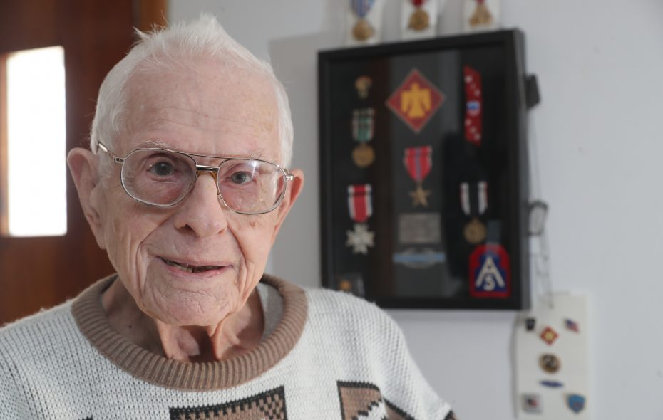 World War II veteran Milton Miller, 93, at at his home, in Amherst, N.Y., on Thursday, Dec. 13, 2018. Behind him are his framed military medals and the German prisoner of war identification tag he had to wear after being captured. (John Hickey/Buffalo News)